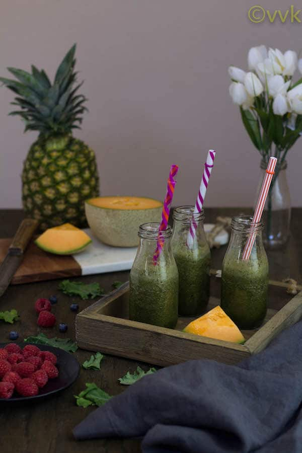 Kale Smoothie with Berries with colorful straws in the jars
