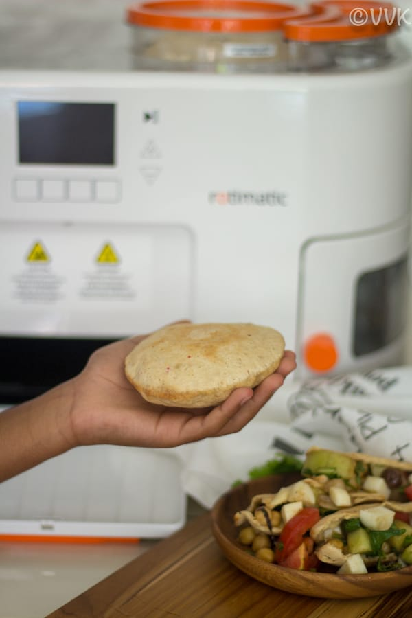 Holding a Rotimatic Pita Bread in hand