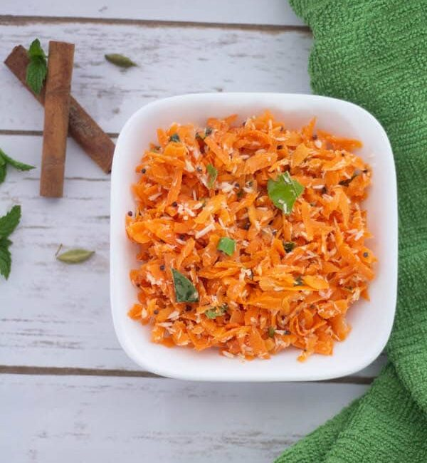 Carrot Coconut Salad or Carrot Kosambari served in a white bowl with two cinnamon sticks below it