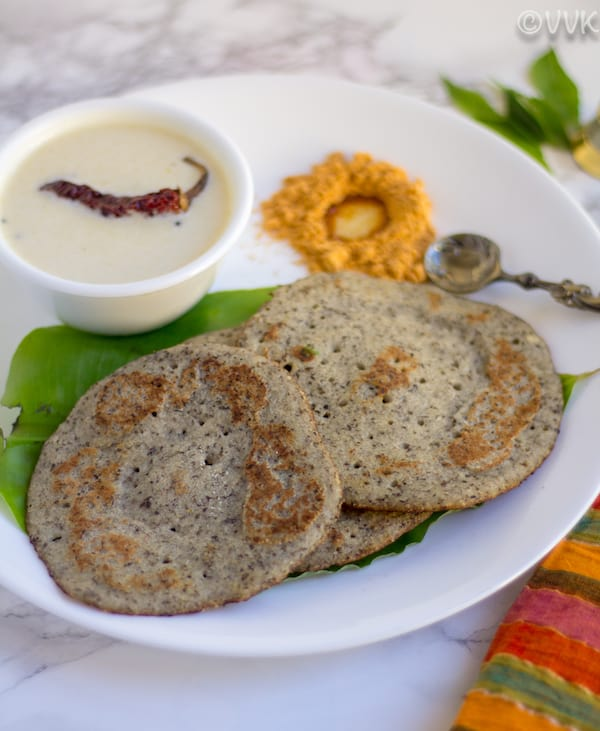 dosai kept on a white plate with chutney and podi