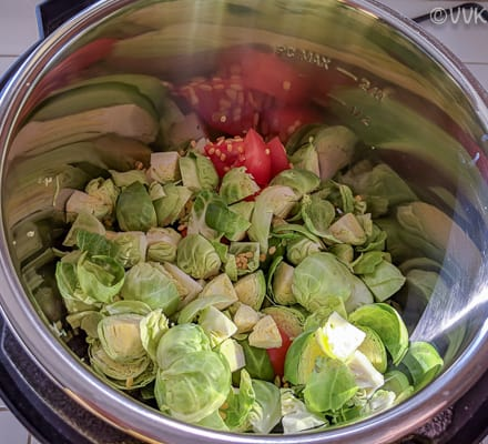 Adding chopped brussels sprouts, ground masala, diced tomatoes and moong dal
