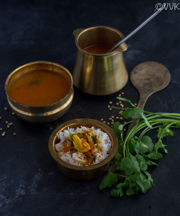 rasam in a brassware served along with rice with cilantro on the side
