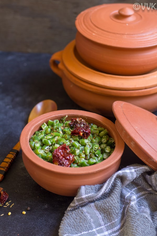 green beans poriyal in a clay pot with a wooden spoon on the side