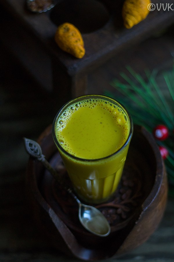 Easy Turmeric Milk - Golden Milk - Slightly Angled Overhead Shot on the Cup with a Few Ingredients Around It
