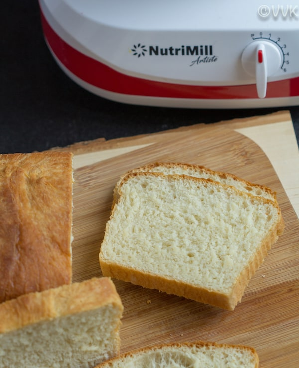 Delicious pieces of Homemade White Bread cut on a wooden board with NutriMill in the background