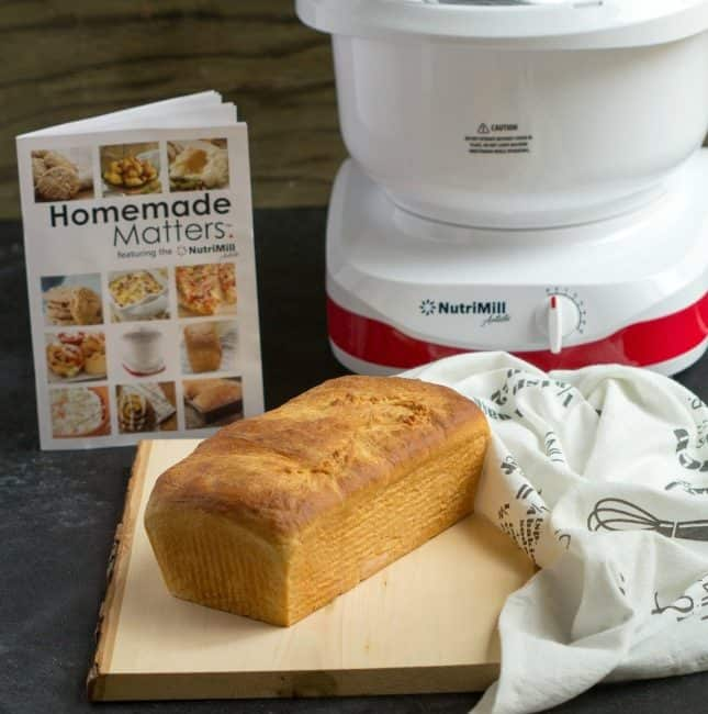 Homemade White Bread on a wooden table with NutriMill set in the back