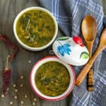 Instant Pot Green Lentils and Spinach Curry - Dal Palak - Beautiful Composition of the Dish with Two Wooden Spoons and Chili Pepper on the Side