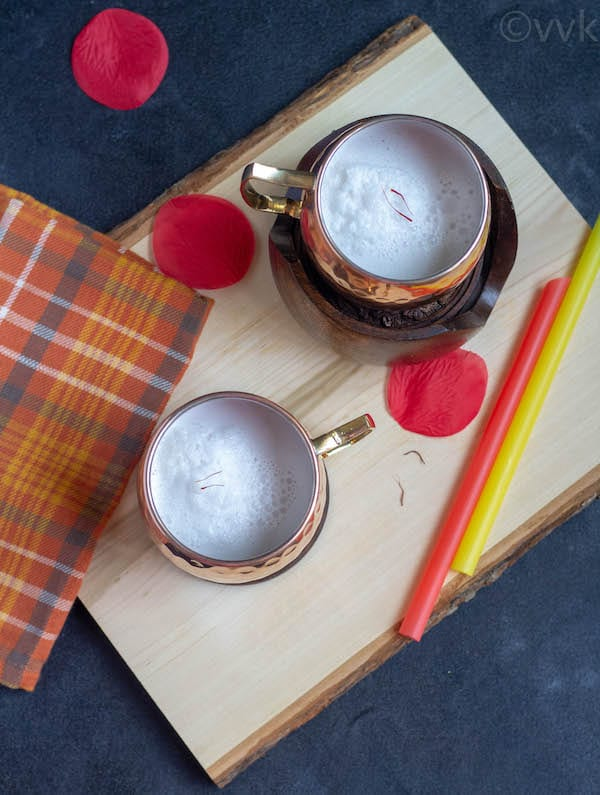 top angle shot of elaneer payasam on a wooden board with straws on the side