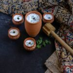 neer mor in clay tumbler and with four small clay tumblers around