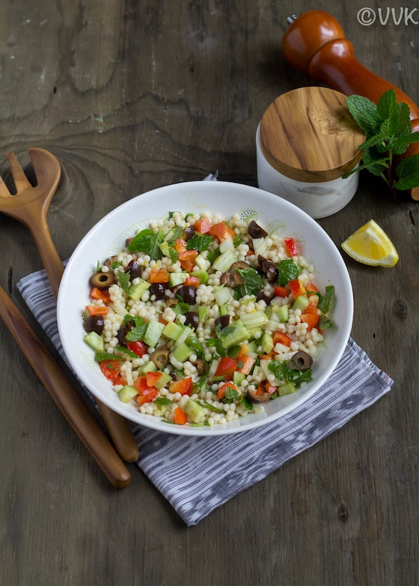 mediterranean couscous salad with lemon wedge and salt on the side