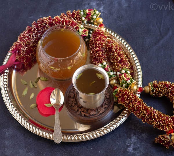 panagam in a silver tumbler on a plate with garland