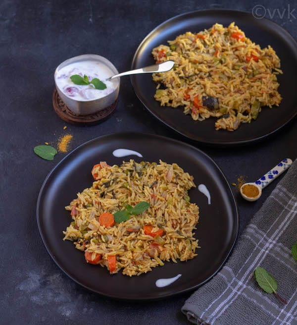 delhi biryani in two black plates with raita on the side
