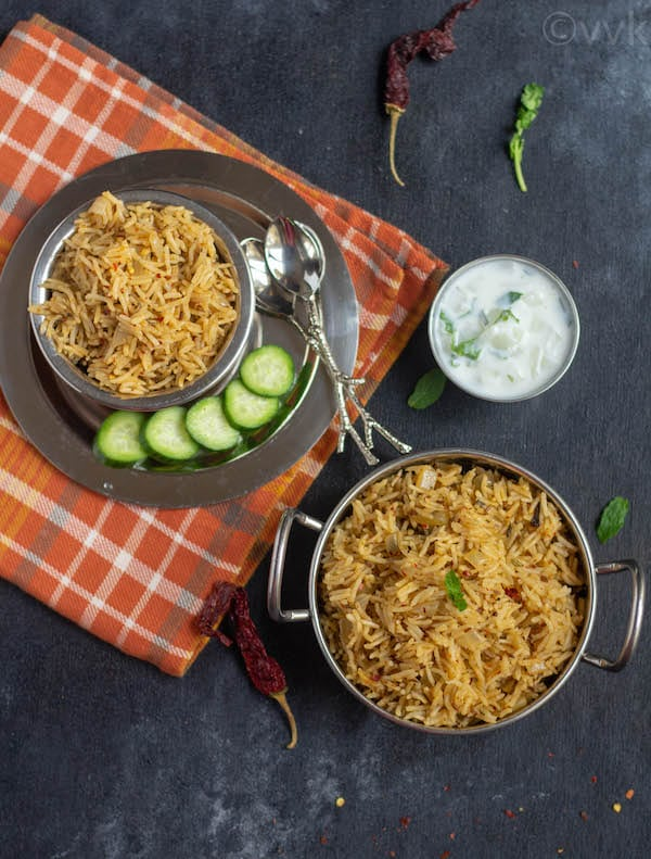 top angle of gongura pickle pulav in two bowls with raita and cucumber