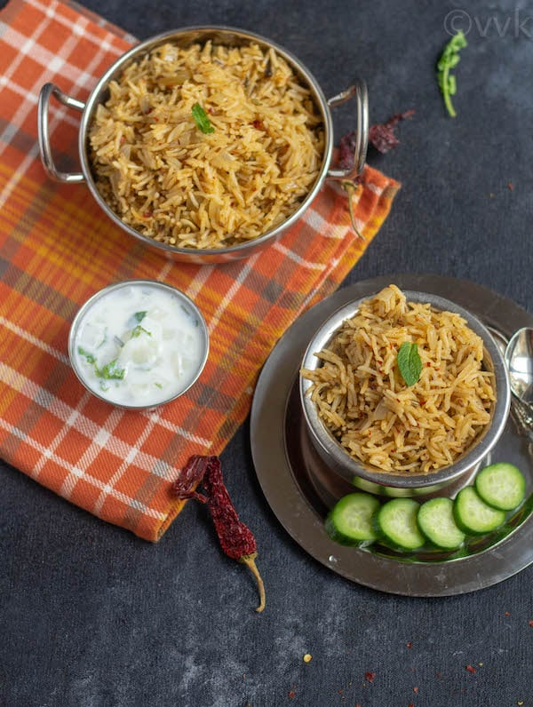 gongura pickle pulav in bowl on a plate with raita and cucumber