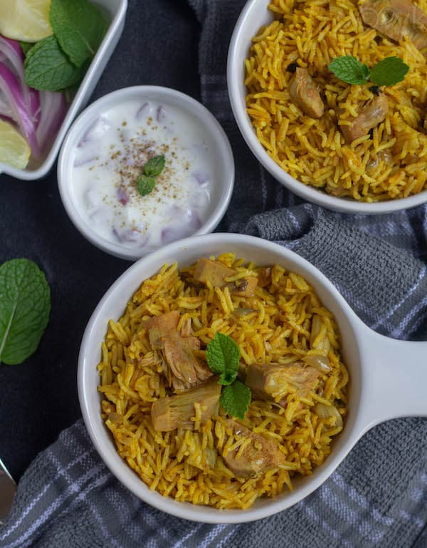 tender jackfruit biryani in two serving bowls with raita