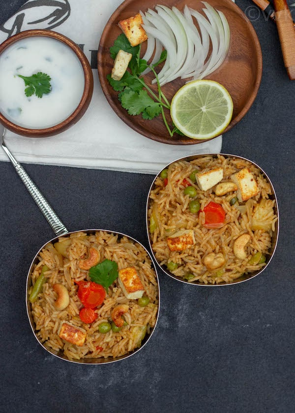 lucknowi veg biryani in two bowl with condiments on the top