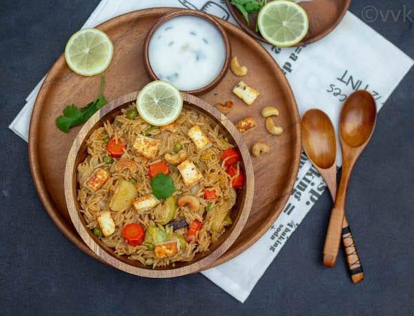 lucknowi veg biryani in a wooden bowl on a wooden plate