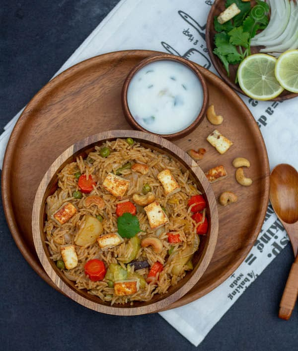 lucknowi veg biryani on a wooden bowl - top angle