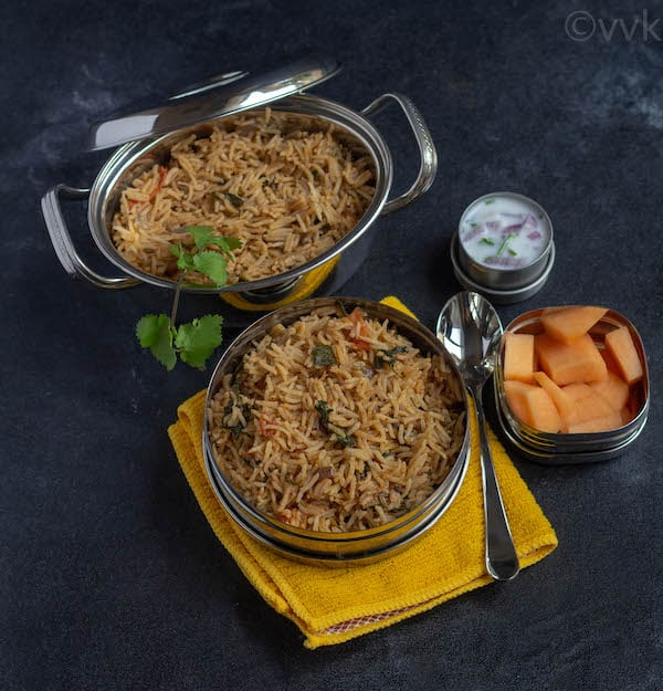 methi pulav in a lunch box on a yellow fabric