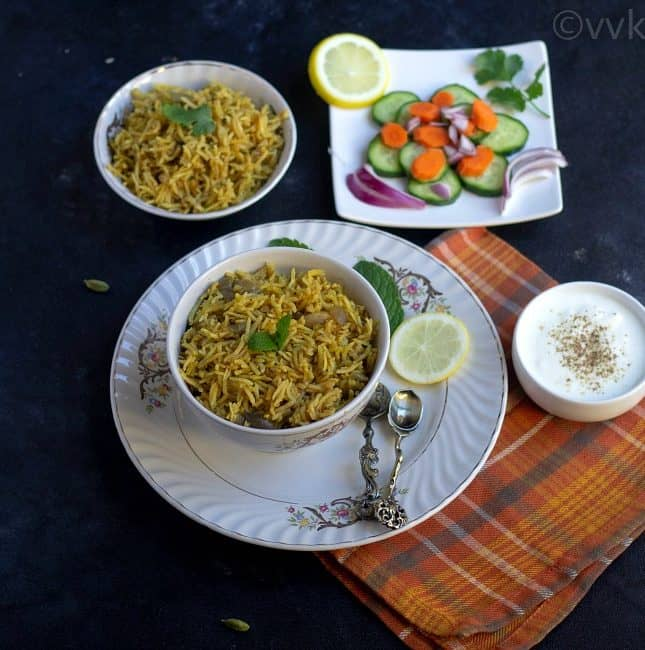onion biryani in a bowl kept on a plate with raita and raw vegetables