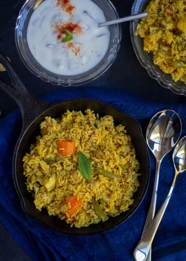 rawther biryani with raita and salna served in cast iron pan