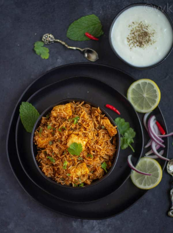 top angle of paneer makhani biryani on a black bowl on a black plate