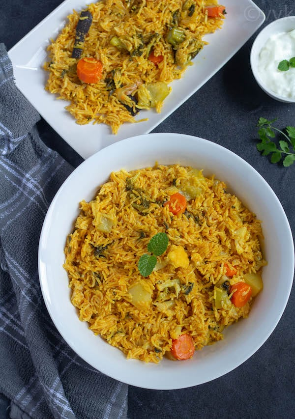 hyderabadi biryani in a bowl with a gray fabric on the side