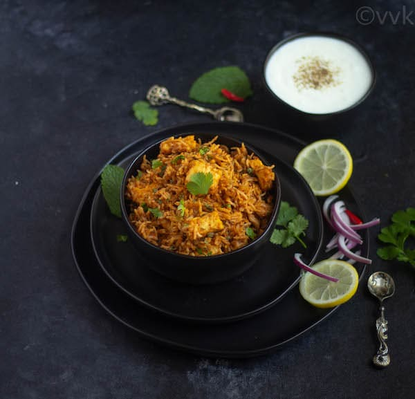 paneer makhani biryani in a bowl with onion and lemon slices on the side