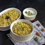 qubooli biryani in white ceramic pot with whole spices on the side