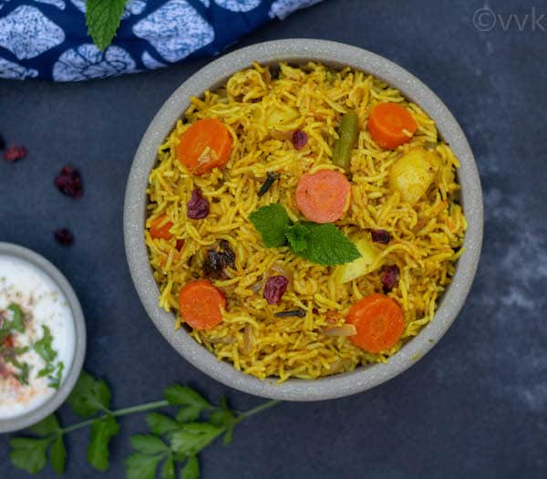 top angle of sindhi veg biryani with raita on the side