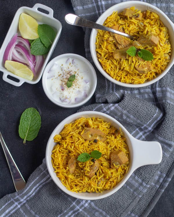 jackfruit biryani in two bowl with raita and onions and lemon wedges