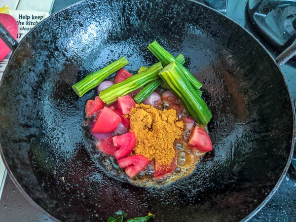 adding the vegetables for dhaniya kuzhambu