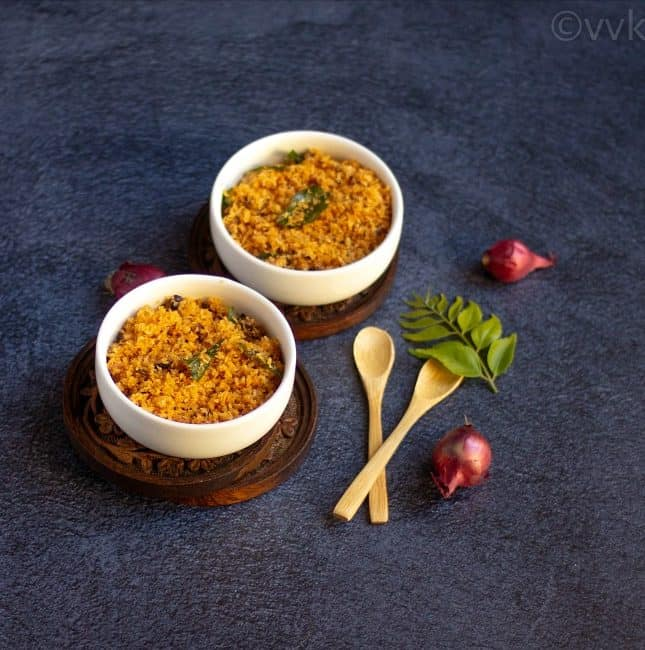 dry coconut chutney in two white bowls with wooden spoons on the side