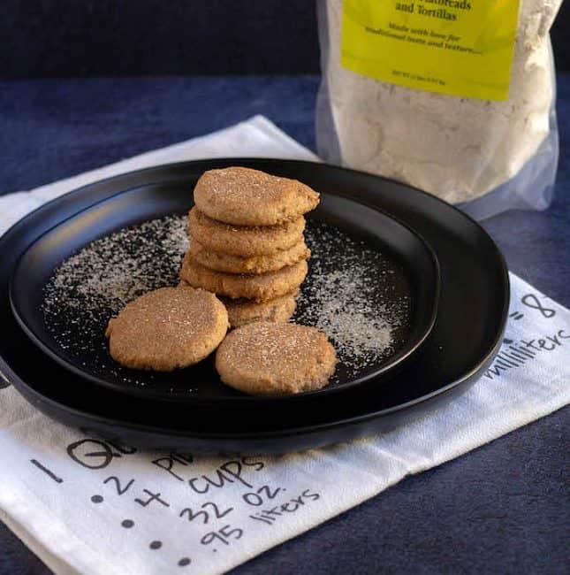 sugar cookies on a black plate sprinkled with sugar