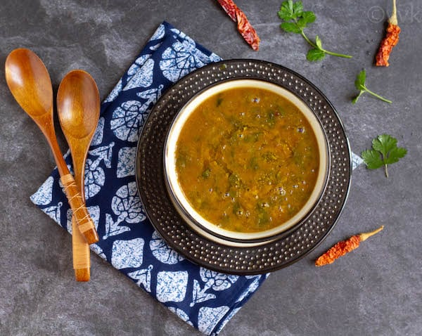 simple dal tadka on a brown bowl placed on a plate which is placed on a blue napkin