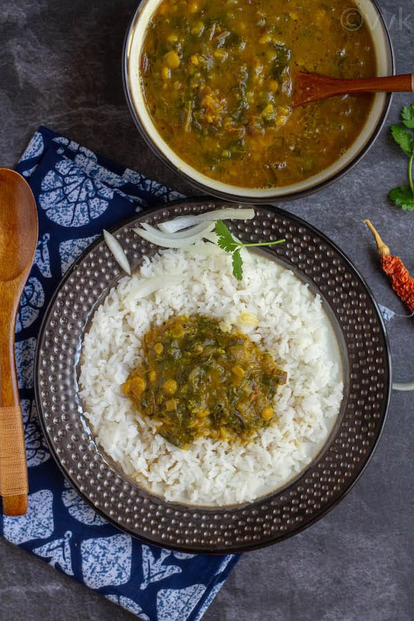 beet green dal with rice on a brown plate and the dal in a big brown bowl