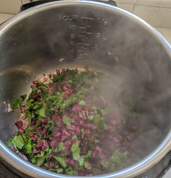 adding beet greens to the sauteed onions
