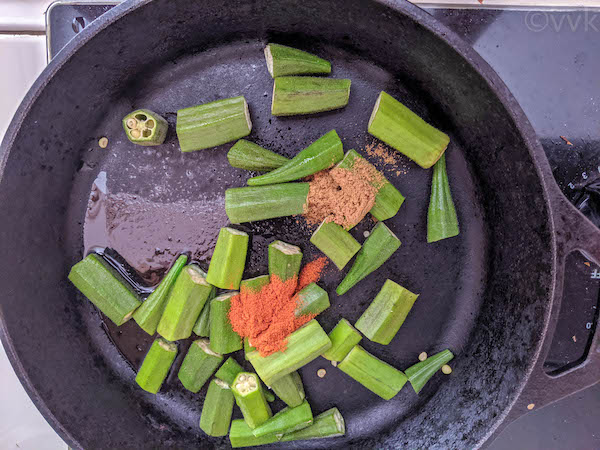 adding okra with spices in a pan