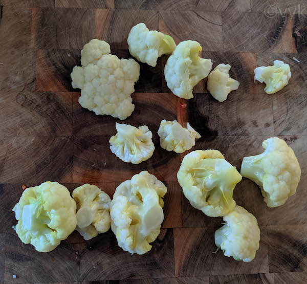 breaking the cauliflower into small florets