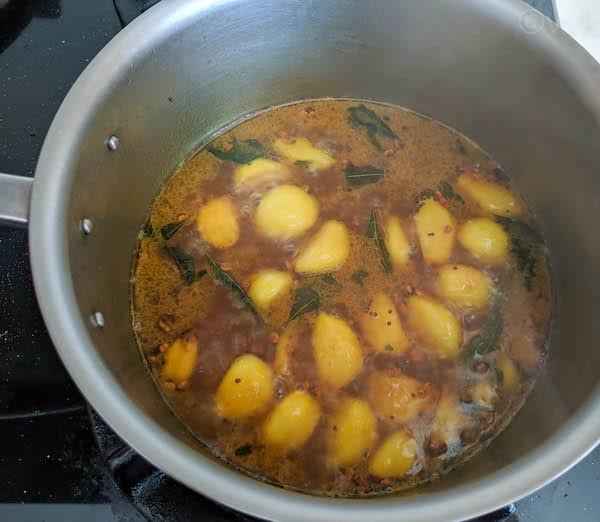 poondu kuzhambu with tamarind water simmering