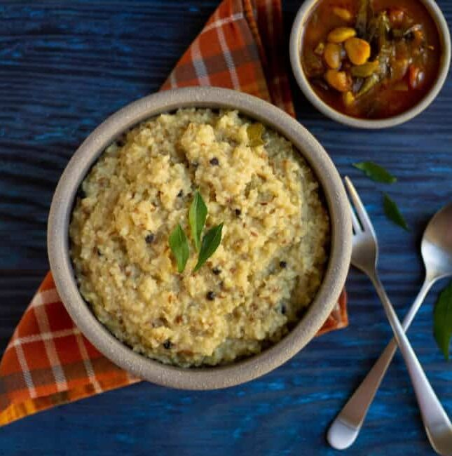 quinoa and millet ven pongal on a clay bowl with gojju on the side