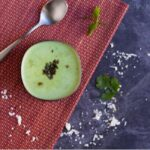 coconut cilantro raita in a silver bowl placed on a red mat