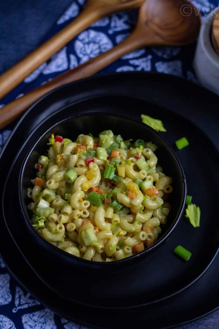 classic pasta salad in a black bowl with some celery greens on the side.