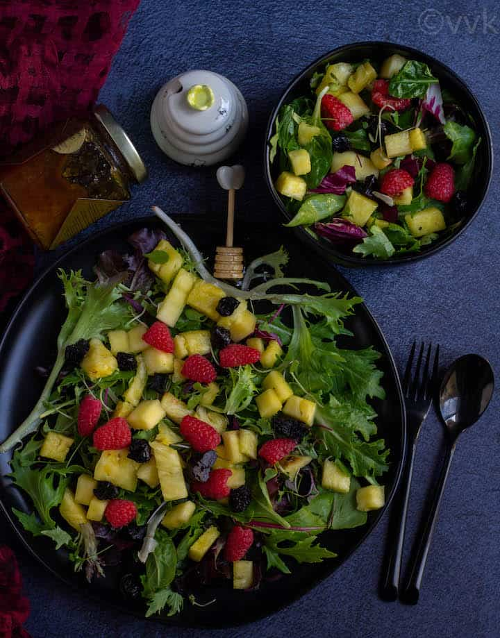 greens and fruit salad in a black plate and bowl with honey on the top