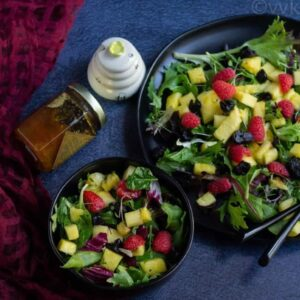 mixed greens and fruit salad in a black bowl and plate with honey on the side