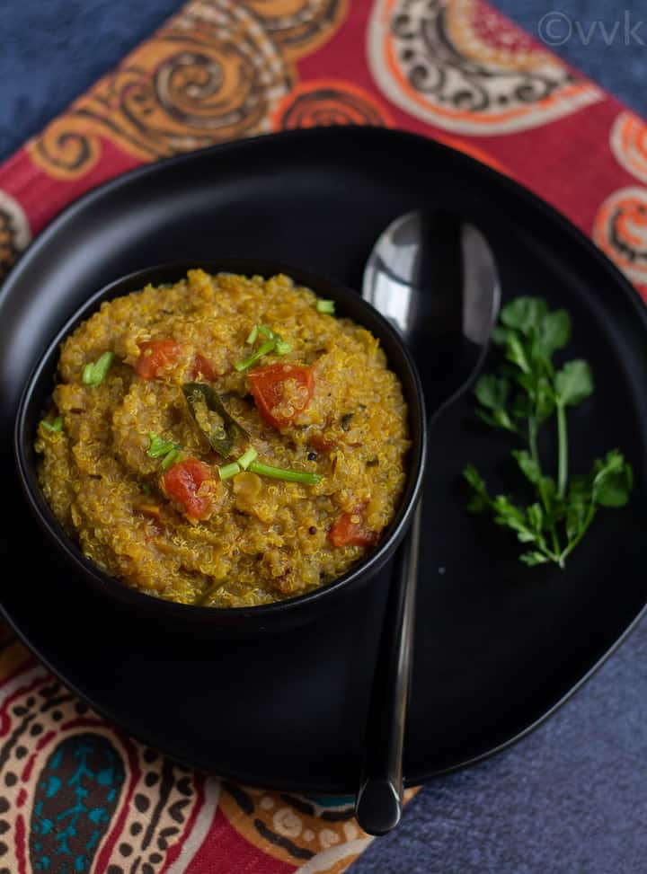 quinoa rasam rice on a black bowl placed on a black plate on a red fabric