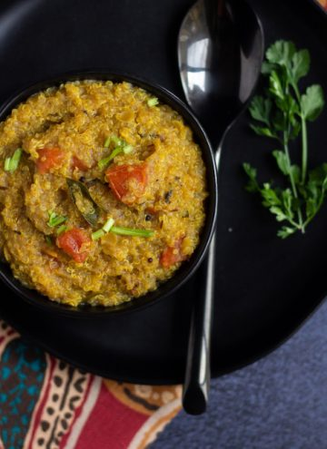 one pot rasam rice place on a black bowl with cilantro and a spoon on the side