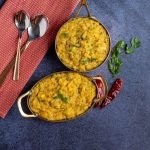quinoa sambar sadham in tow brassware with red chilies on the side