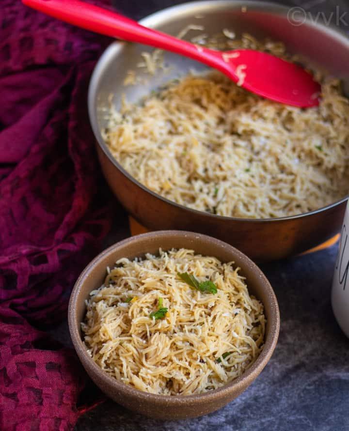 simple semiya upma in a bowl with sugar on the side and pan full of semiya behind