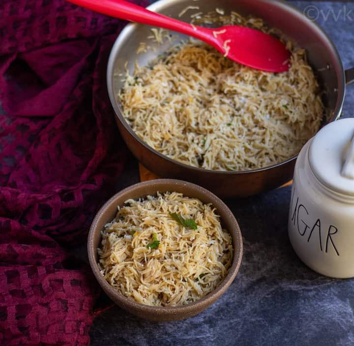 semiya upma in a ceramic bowl with sugar cannister next to it and pan full of semiya behind it